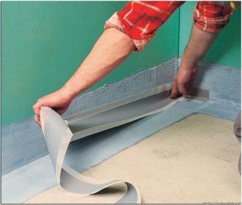 Наклейка герметизирующей ленты на стыке пола и стены